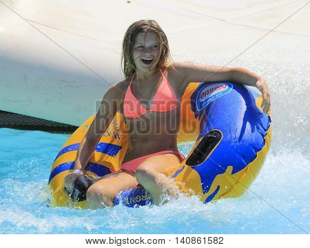 Rhodes Greece-July 29 2016: The girl joying after rafting slide in the Water park.Rafting slide is one of many popular game for adults and children in park.Water Park is located  on the island of Rhodes in Greece and one of the most popular