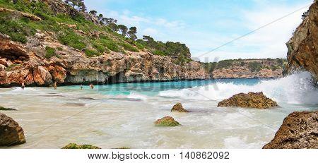 Cala Llombards Majorca Spain - June 22 2008: Bay Calo d'Es Moro - people bathing in the ocean / mediterranean sea - view through rocks
