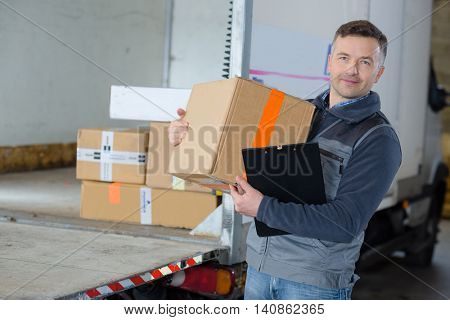 delivery man holding box in front of his truck