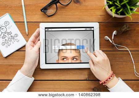 business, education, technology, people and internet concept - close up of woman with internet browser search bar on tablet pc computer screen on wooden table