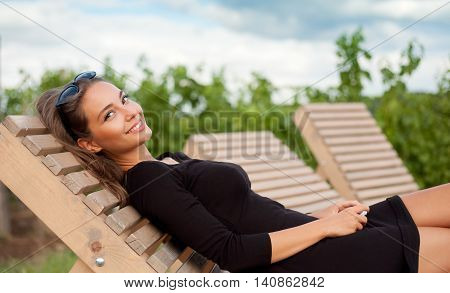 Outdoors portrait of gorgeous young brunette woman on relaxing on tanning bed.