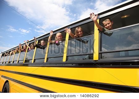 Elementary school students waving from school bus