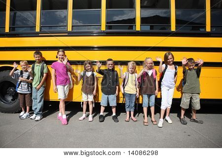 Elementary school students lined up by bus