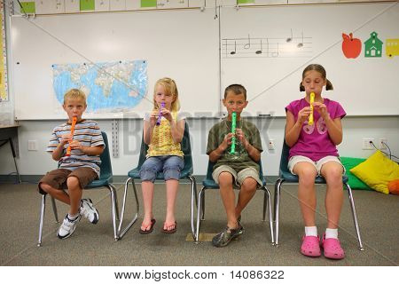 Elementary school students playing flutes
