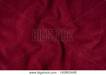 Red wrinkled fabric texture. Close-up of soft cotton cloth may be used as background.