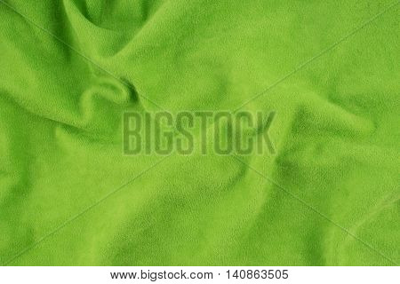 Green wrinkled fabric texture. Close-up of soft cotton cloth may be used as background.