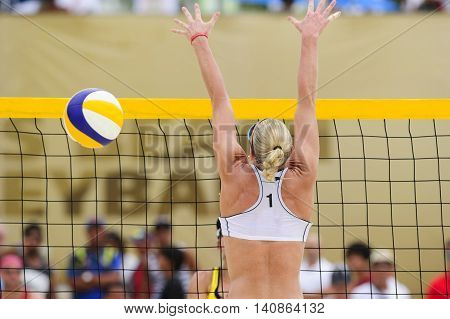 Volleyball player is a female athlete volley ball player at the net attempting to block the ball.