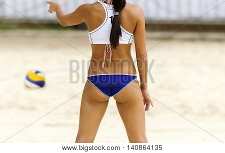 Volleyball player is a female athlete volley ball player giving direction while getting ready for the next point to begin..
