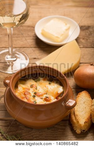 Onion soup with its ingredients on the wooden table (french cuisine)