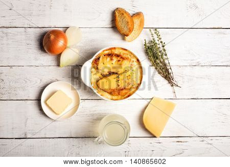 Onion soup with its ingredients on the white table (original french cuisine)