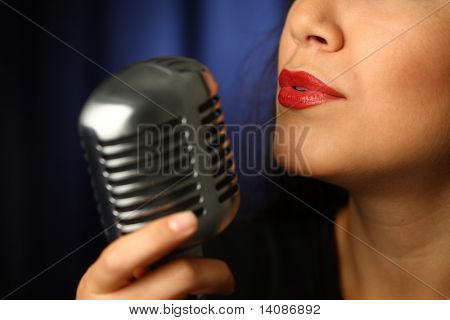 Close up of woman singing into vintage microphone