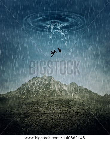 A silhouette of an young man with an umbrella falling from the rainy sky as a splash of water crashing down to the cracked desert ground. Business risk fail and loss concept