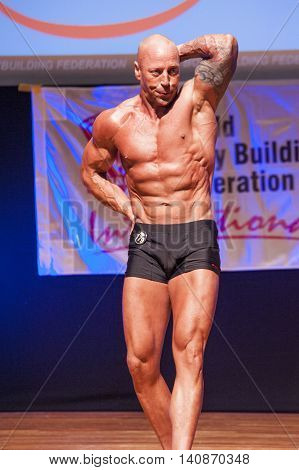 MAASTRICHT THE NETHERLANDS - OCTOBER 25 2015: Male bodybuilder Erik Stobbe shows his best abdominal and thighs pose at the World Grandprix Bodybuilding and Fitness of the WBBF-WFF on October 25 2015 at the MECC Theatre in Maastricht the Netherlands.