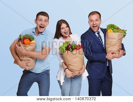 Happy people, two men and young woman hold shopping paper bags full of groceries, vegetables and fruits isolated at blue background. Healthy food shopping, excited buyers