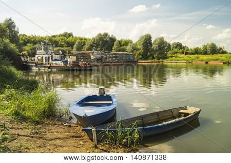 Boats beside coast on background old motorboat and blue sky with cloud