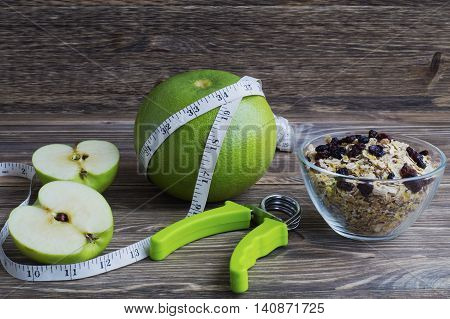 The concept of a healthy lifestyle. Green fruits oatmeal with raisins measuring tape and hand espander.