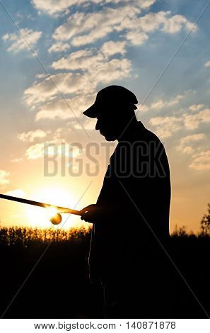 silhouette of a fisherman with a fishing rod