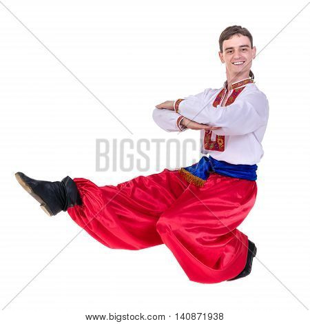 young man wearing a folk russian costume dancing against isolated white background with copyspace