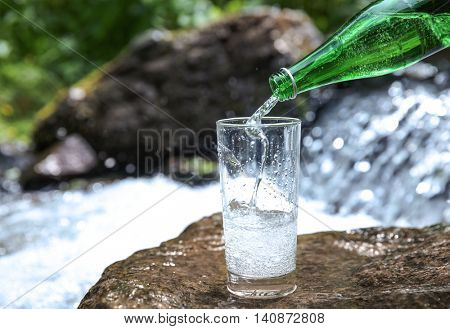 Pouring water in cup on small waterfall background