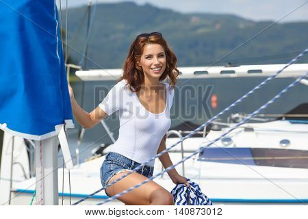 woman wearing sea cloths and sexy sailor T-shirt. Attractive woman on a yacht on summer day