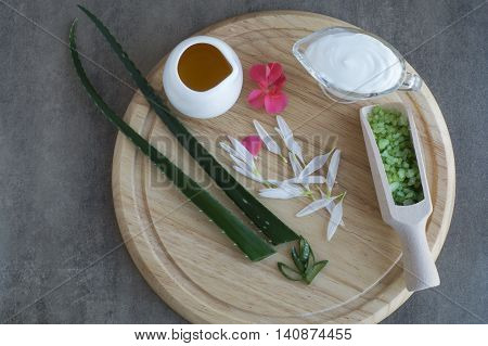 Natural cosmetic ingredients. Aloe vera oil sea salt handmade cream on a wooden board. Spa concept, flat lay.