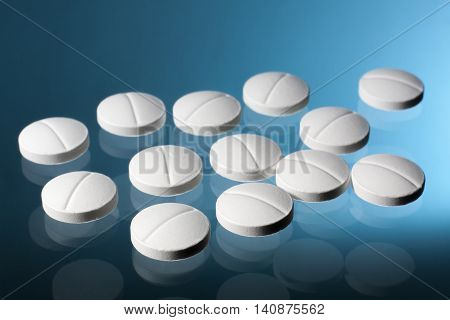 White pills tablets with a blue background