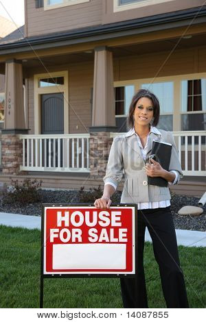 Female Realtor standing by FOR SALE sign