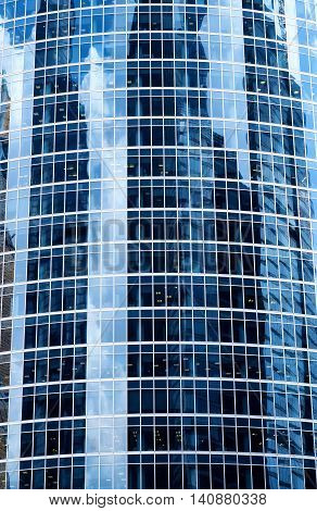 A background with the reflections of sky, clouds and buildings in the windows of a skyscraper.
