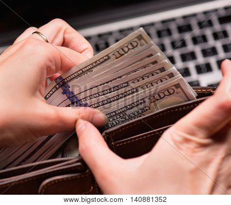 Close up of female hands counting US dollar banknotes at the table in front a laptop computer. Woman accountant with money and notebook.