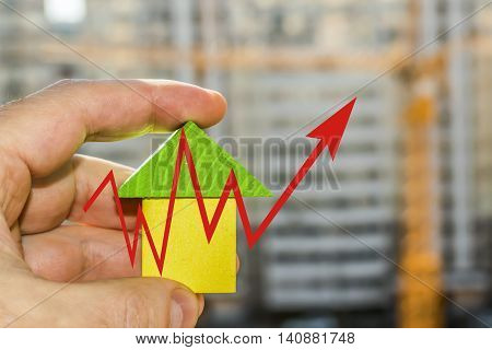 Wood house in hand on a background of construction   The concept of price changes on the real estate market .