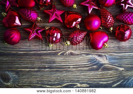Pink Christmas toys on a brown wooden background with copy spase, top view. The concept of Christmas cards. New year wallpapers.