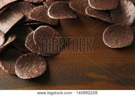 Chocolate crisps on wooden background