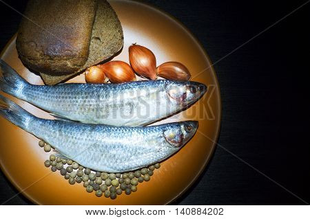 Two fish Golden grey mullet with onion allspice and rye bread on the plate on black background.