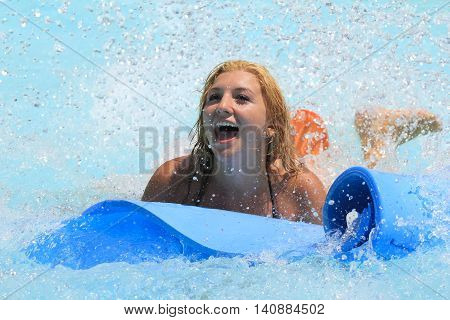 Rhodes Greece-July 30 2016:The girl joying after mat racer slide.Mat racer slide is very popular for young people in the Water Park.Water Water Park is located on the island of Rhodes in Greece and one of the most largest in Europe and is a very popular