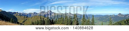 Panoramic of the Tannheim Valley in Tyrol, Austria; mountains and valleys, rugged peaks of the Gaishorn and Einstein; villages in the valley, blue sky with white clouds