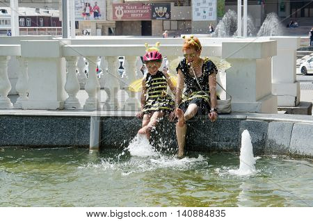 Kharkiv Ukraine - June 18 2016: Mother and daughter dreessed in costumes of bees are drying their feet after washing them in the fountain. Costumed bike ride