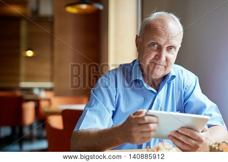 Portrait of senior man using touchpad at cafe