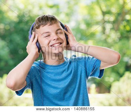 Teen boy smiling listening a music in headphones, posing outdoors.