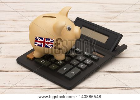 The Great Britain Pound currency A golden piggy bank and calculator on a wood background with British flag