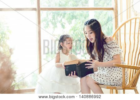 Family, Children, Education, School And Happy People Concept - Happy Mother And Daughter Reading Boo