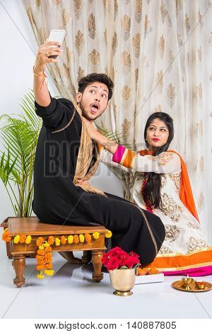 Indian brother taking selfie with sister on Raksha Bandhan festival after tying knot or rakhi