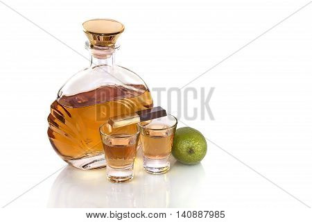 Bottle tequila with shot glasses and chocolate with lime on white background