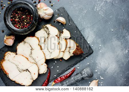 Chicken pastrami with pepper and garlic on a stone plate top view blank space for text