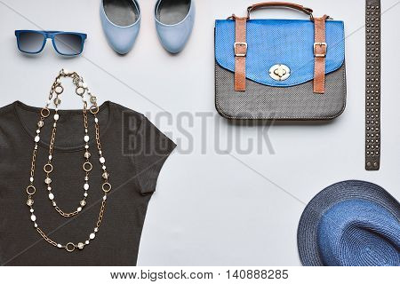 Fashion woman clothes accessories set. Creative hipster stylish handbag black top glamor shoes trendy necklace blue hat and sunglasses.Unusual urban summer outfit. Overhead top view gray background