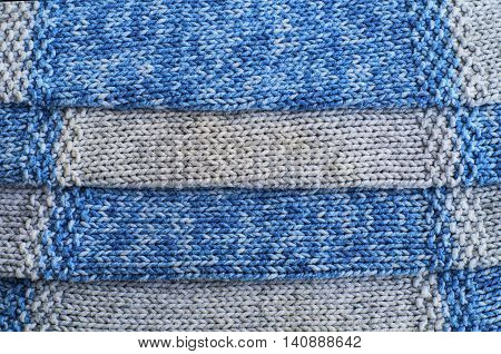 Knitted gray and blue wool pattern close up.