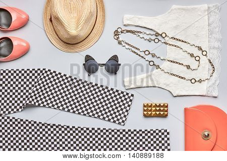 Street style Fashion summer clothes accessories set. Stylish girl, handbag clutch, white top, leggings, glamor orange shoes, trendy necklace hat, sunglasses. Bright outfit. Overhead on gray background