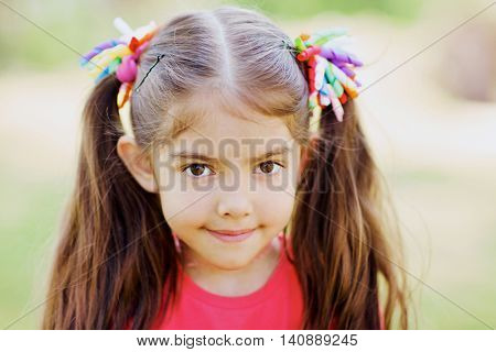 Portrait of cute little girl with two ponytails outdoors
