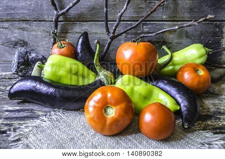 Ripe tomatoes, eggplant and peppers on the background of the old of burnt boards