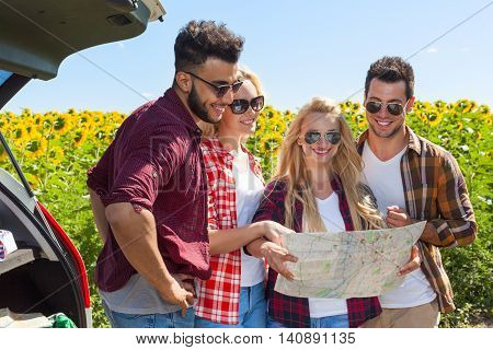 People group looking road map standing sunflowers field outdoor, two couple near car summer day holiday trip