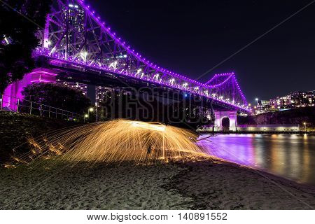 Brisbane Story Bridge by night in magenta with steel wool spinning on beach - close up